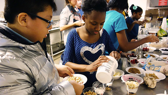 Middle- and high-school students work together to make yogurt parfaits for dessert